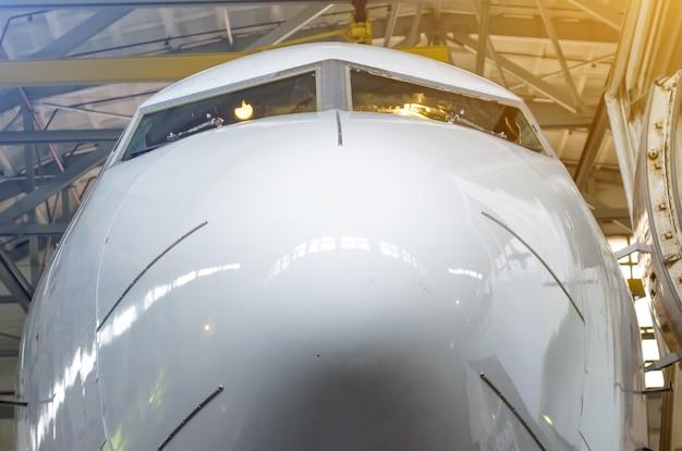 Nase des flugzeugs und des cockpits in der nähe des hangars.