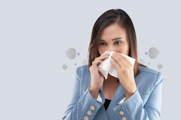 Nasenbrennen der geschäftsfrau wegen des giftigen rauches und der partikel in der luft. frau mit allergie, ein taschentuch auf seiner nase haltend
