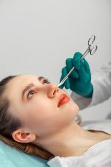 Nasenkorrektur, die hände des chirurgen berühren die nase des patienten. menschen, kosmetik, plastische chirurgie und schönheitskonzept - chirurgen- oder kosmetikerhände berühren weibliches gesicht. platz kopieren.
