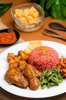 Nasi lemak mit drachenfruchtreis serviert mit chicken rendang und scharfer sauce sambal