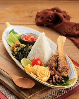 Nasi lemak oder nasi campur, indonesischer balinesischer reis mit kartoffelpuffer, sate lilit, gebratenem tofu, eiern und erdnuss