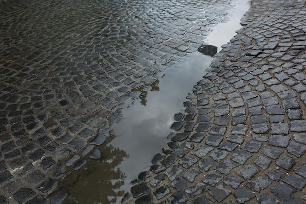 Nass gealterte pflastersteine nach dem regen mit wasserpfütze. lemberg, ukraine