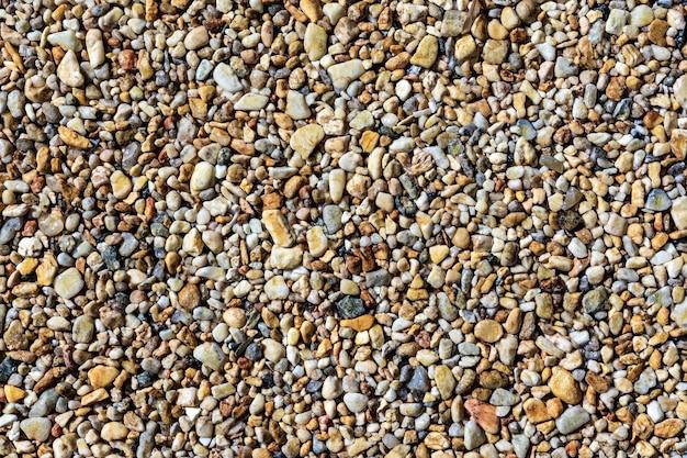 Nasse meereskiesel in verschiedenen farben als natürlicher hintergrund ein muster aus kleinen glatten steinen