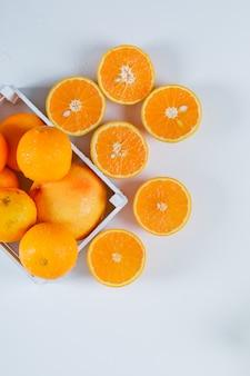 Nasse orangen mit hälften in einer weißen rechteckigen schüssel auf weißer oberfläche, flach legen.