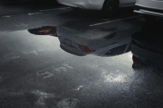 Nasse parkplätze nach starkem regen fallen mit reflexion des autos in pfütze auf dem boden. selektiver fokus.