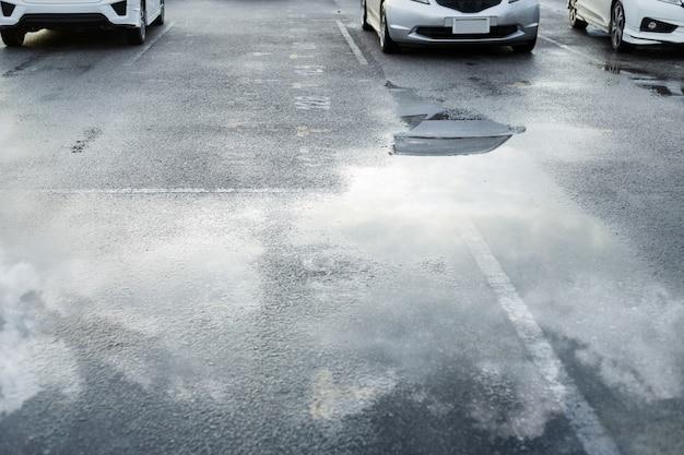Nasse parkplätze nach starkem regen fallen mit reflexion des himmels in pfütze auf dem boden. selektiver fokus.