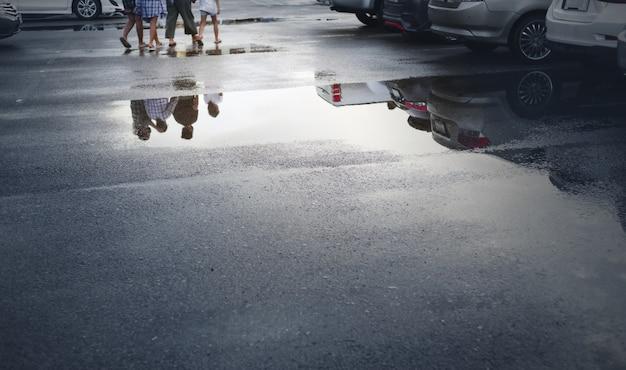 Nasse parkplätze nach starkem regen fallen mit reflexion von autos und gehenden menschen in pfütze auf dem boden. selektiver fokus.