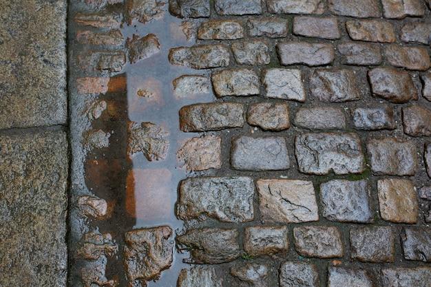 Nasse pflastersteine nach dem regen in der fußgängerzone. nahaufnahme