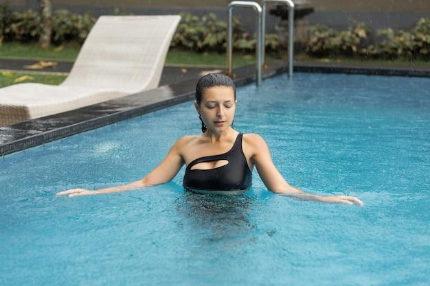 Nasse sexy blackhair frau im badeanzug, der am pool aufwirft.