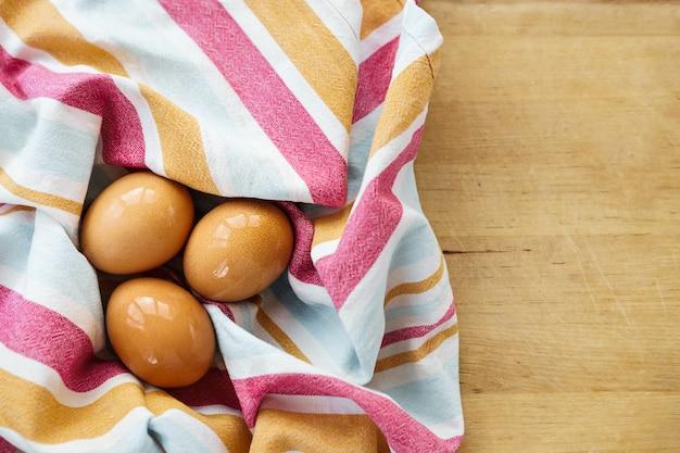 Nasse unbemalte eier liegen auf einem gestreiften handtuch