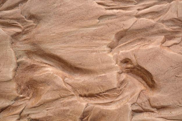 Nasser brauner sandnaturtexturhintergrund. draufsicht