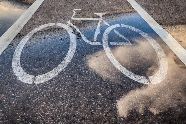Nasser fahrradweg und reflexion der wolken