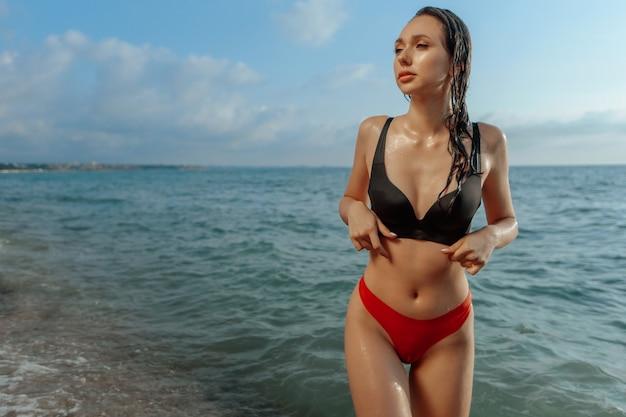 Nasses sexy mädchen im badeanzug kommt aus dem meer