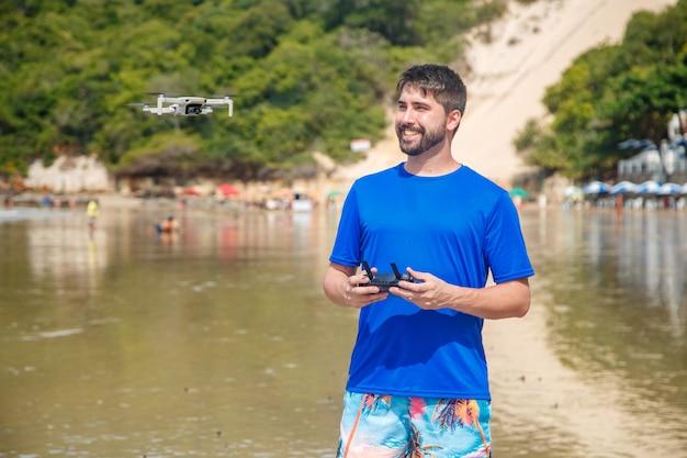 Natal, rio grande do norte, brasilien - 12. märz 2021: mann mit drohne am strand von morro do careca in natal