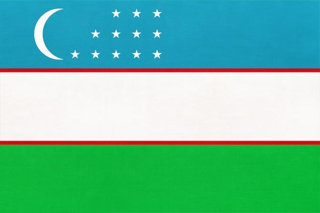 Nationale gewebeflagge der republik usbekistan, textilhintergrund. symbol des weltasiatischen landes.