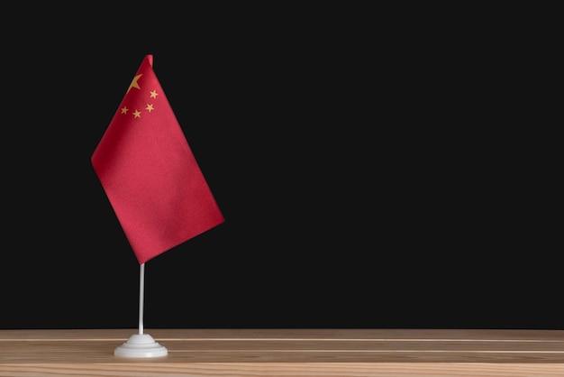 Nationale tischflagge von china auf schwarzem hintergrund. rote fahne mit sternen.