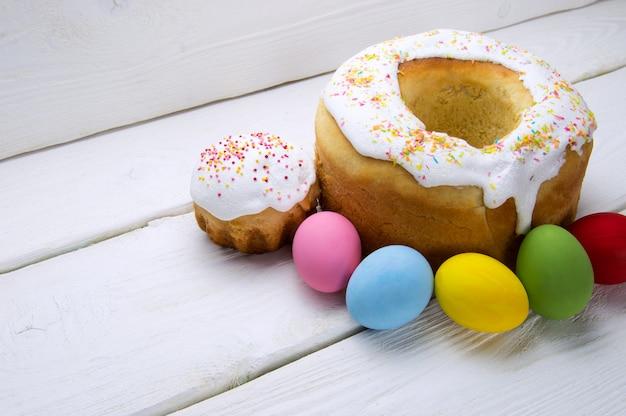 Nationaler russischer feiertag ostern-kuchen und farbige eier auf weißer holzoberfläche