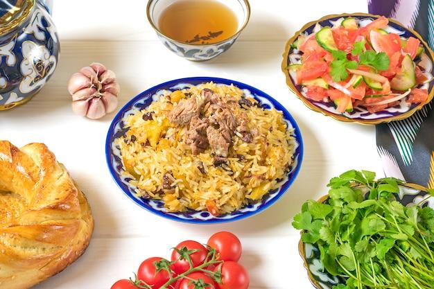 Nationaler usbekischer pilaw mit fleisch, achichuk-salat aus tomaten, gurken, zwiebeln in teller mit traditionellem