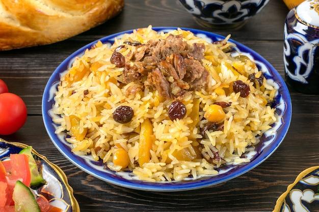 Nationaler usbekischer pilaw mit fleisch im teller mit traditionellem muster auf dunklem holztisch draufsicht