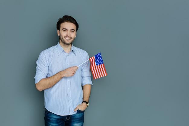Nationales gefühl. freudiger positiver patriotischer mann, der die us-flagge hält und lächelt, während er stolz auf sein land ist