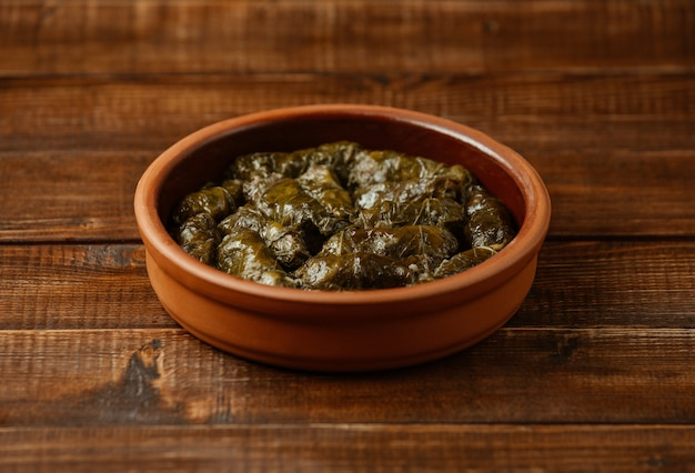 Nationales lebensmittel yarpaq dolmasi, weinblätter mit fleisch nach innen, gekocht innerhalb einer tonwarenschüssel