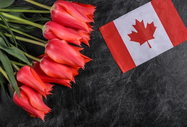 Nationalfeiertag. blumenstrauß aus tulpen und kanada-flagge auf einer tafel. zurück zur schule