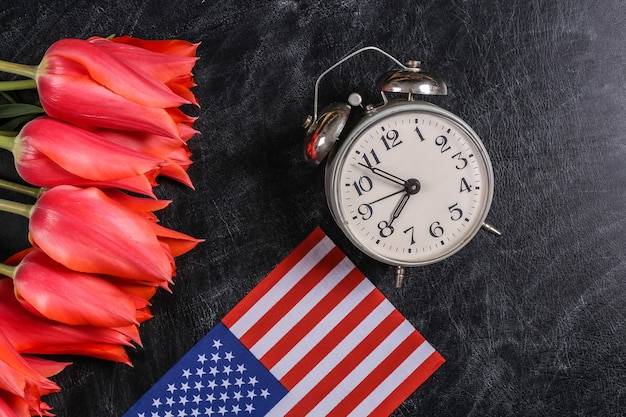 Nationalfeiertag. blumenstrauß aus tulpen, wecker und usa-flagge auf einer kreidetafel. zurück zur schule