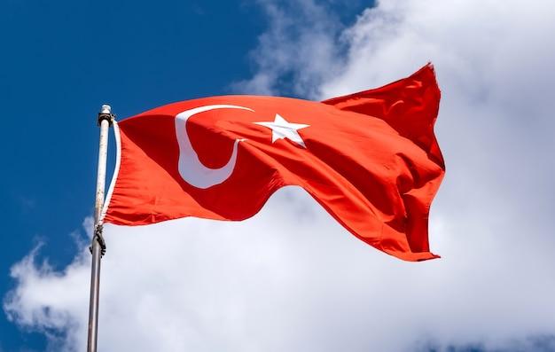 Nationalflagge der türkei, die auf blauem himmel weht