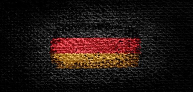 Nationalflagge deutschlands auf dunklem stoff.