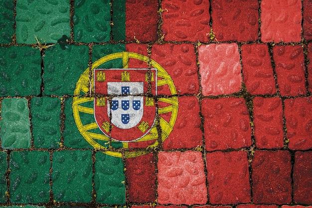Nationalflagge portugals auf steinmauerhintergrund. flaggenfahne auf steinbeschaffenheitshintergrund.