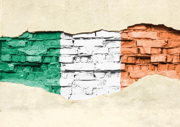 Nationalflagge von irland auf einem backsteinhintergrund. backsteinmauer mit teilweise zerstörtem putz, hintergrund oder textur.