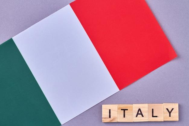 Nationalflagge von italien. holzwürfel mit buchstaben lokalisiert auf violettem hintergrund.