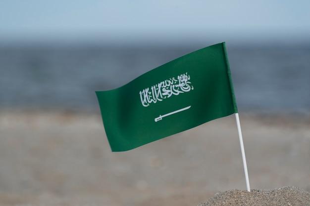 Nationalflagge von saudi-arabien auf seehintergrund. grüne flagge mit schwert.
