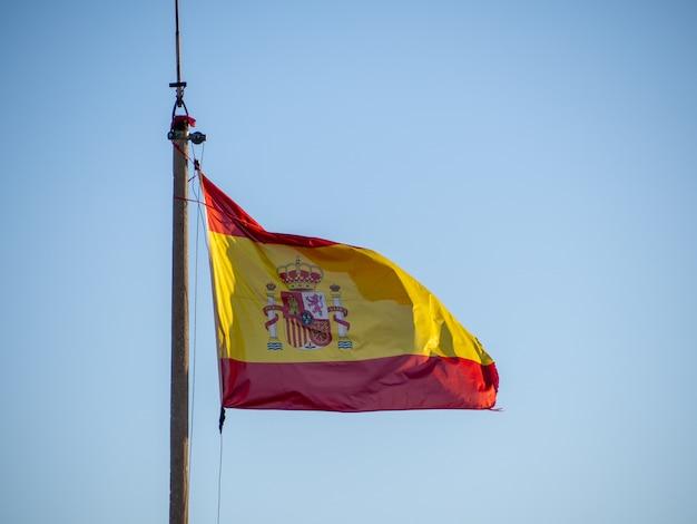 Nationalflagge von spanien, die auf dem fahnenmast über einem klaren blauen himmel weht