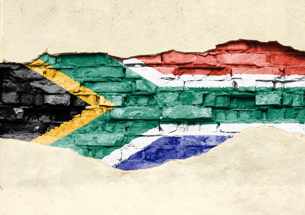 Nationalflagge von südafrika auf einem backsteinhintergrund. backsteinmauer mit teilweise zerstörtem putz, hintergrund oder textur.