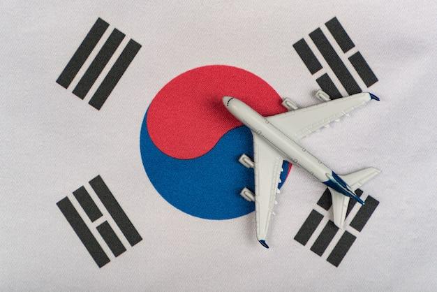 Nationalflagge von südkorea und das modellflugzeug schließen. wiederaufnahme der flüge nach quarantäne