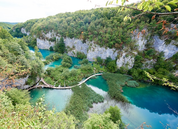 Nationalpark plitvicer seen - unesco-weltkulturerbe. luftaufnahme des beleuchteten sonnengrünen waldes auf felsigen klippen und der langen holzbrücke mit touristen über seen mit klarem blaugrünem wasser.