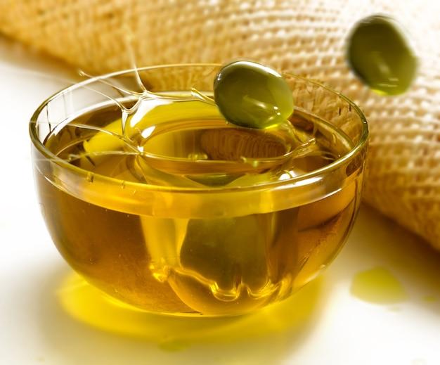 Natives olivenöl extra mit oliven in einer schüssel Premium Fotos