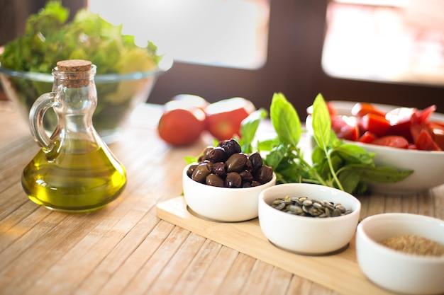 Natives olivenöl extra und oliven im vordergrund mit frischem gemüse und sonnenlicht im hintergrund - mediterranes diätkonzept