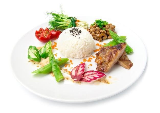 Natto mit reis und grill schweinefleisch japan fusion-stil lebensmittel gesunde mini-beilage dekorieren erbsensprossen rollsalat sasemi-sauce spargel, eingelegte gurke und radieschen seitenansicht isoliert weißen hintergrund