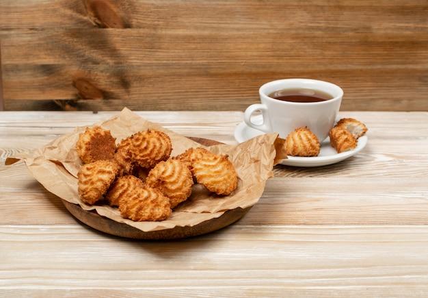Natürlich gebackene kokosnusskekse oder kokosmakronen mit tee oder kaffee. hausgemachte diätplätzchen mit kokoschips auf holztischseitenansicht