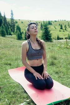 Natürlich, sport, gesundheit, menschen, lifestyle-konzept - gesunde junge, unabhängige yogapraktikerin, die meditation praktiziert und eine schöne, ruhige aussicht auf die berge mit blick auf die reinheit posiert