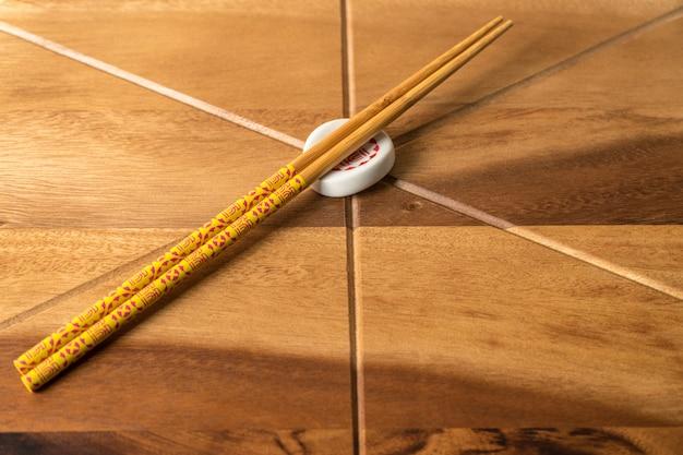 Natürliche bambus-chopsticks auf holztischhintergrund