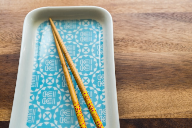 Natürliche bambus-chopsticks und platte auf holztischhintergrund