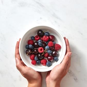 Natürliche bio-früchte, beeren in einem teller auf grauem steinhintergrund. konzept der gesunden nahrung mit kopienraum. flach liegen.