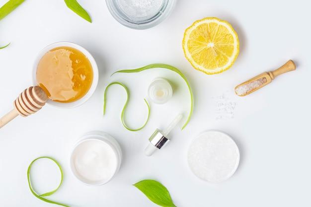 Natürliche bio-inhaltsstoffe für die häusliche hautpflege. kosmetik reinigen und pflegen. schönheitsprodukte: sahne, honig, meersalz zwischen grünen blättern auf weißer oberfläche. flach legen, platz für text kopieren