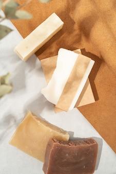 Natürliche bio-kosmetik. draufsicht der handgemachten seife mit handgemachtem leerem band auf doppeltem strukturiertem lederhintergrund mit eukalyptusschatten