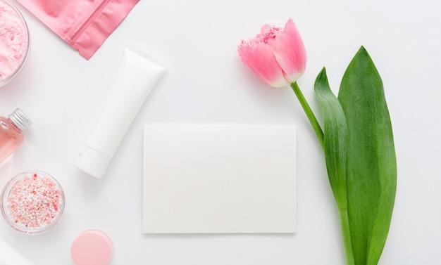 Natürliche bio-kosmetikprodukte mit rosa tulpenblüte. weiße leere modellkarte mit platz für text. kosmetik für bad spa, hautpflege, flat lay