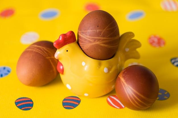 Natürliche bio-ostereier mit hühnerdekoration und gelbem hintergrund als dekoration für ostern