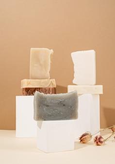 Natürliche bio-selbstpflegeprodukte. turmstapel aus verschiedenen handgemachten seifen und blättern auf cremefarbenem hintergrund. spa-accessoires kreative kunstkomposition auf beigem hintergrund